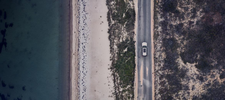 Bil kjører på vei langs kyst