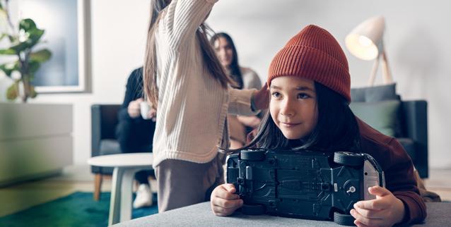 Jente med lekebil sammen med familie
