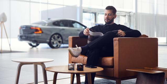 Mann sitter i stol og leser et magasin.