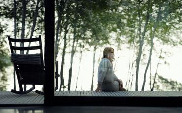 Kvinne sitter på veranda med gyngestol