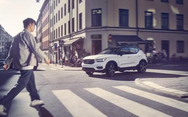 Mann går over fotgjengerfelt med hvit bil i kryss
