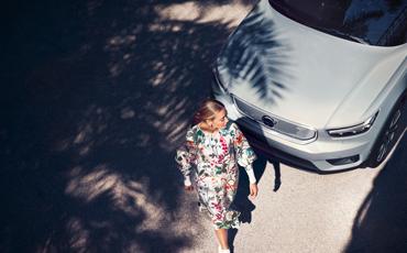 Kvinne går forbi en hvit, parkert bil