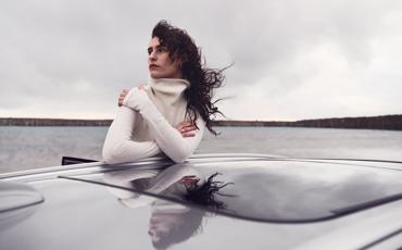 Kvinne lener seg ut av parkert bil i vind