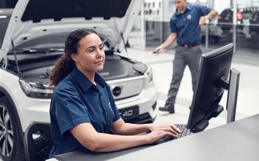 Bilmekaniker skriver på pc i verksted