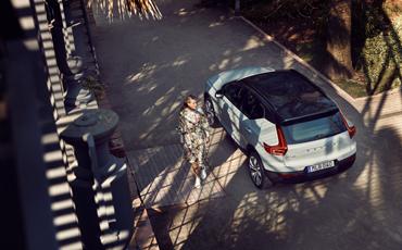 Dame går forbi en parkert bil